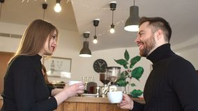A cute couple of young people in a coffee shop, they drink coffee and talk. stock footage