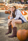 Cute Cowgirl in Hat and Boots at the Pumpkin Patch Royalty Free Stock Photography