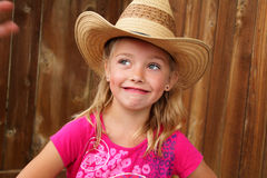 Cute cowgirl in a straw hat. Expression of a cute little blond farm girl in pink shirt and a straw cowboy hat. Shallow depth of field Royalty Free Stock Images