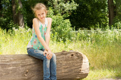 Cute coy little girl sitting on a log in woodland Royalty Free Stock Photo