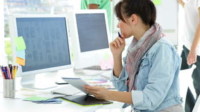 Cute creative designer working sitting at her desk. In creative office stock video