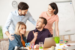 Cute creative team is working in office. I have a great idea. Cheerful young men is talking with his colleagues about a project. He is sitting at desk and using Royalty Free Stock Image