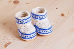 Cute Crochet baby booties  on wooden background. Pair of Cute hand made baby shoes on wooden background Royalty Free Stock Photography