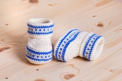 Cute Crochet baby booties  on wooden background. Two Pairs of Cute hand made baby shoes on wooden background Stock Photo