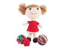 Cute Crocheted Doll In Red Dress. Handcrafted crocheted doll in a red dress with balls of yarn Stock Images