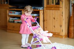 Cute crying baby girl making first steps with doll carriage. Cute adorable crying baby girl making first steps with doll carriage. Beautiful toddler child Royalty Free Stock Image