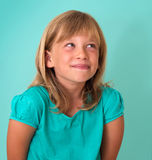 Cute cunning little girl isolated on turquoise background. Human emotion facial expression.