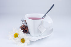 Cute cup with flowers. Strange cup with flowers and cinnamon on white Stock Photo