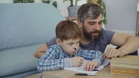 Cute child is writing in notebook with his father sitting near the table and looking at his son. Preschool education. Cute curious child is writing in notebook stock video footage