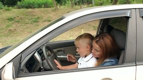 Mother with her son driving a car, mom shows the child how the car works. Cute curious small boy sitting on his mother`s lap behind the steering wheel, he stock video