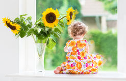 Cute curly baby girl next to sunflower bouquet Royalty Free Stock Image