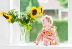 Cute curly baby girl next to sunflower bouquet Royalty Free Stock Images