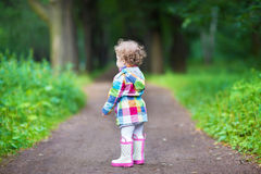 Cute curly baby girl in a park, view from her back stock image