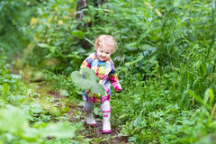 Cute curly baby girl playing with big leaves in park Royalty Free Stock Photography