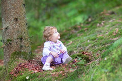 Cute curly baby girl playing in pine wood forest Royalty Free Stock Image