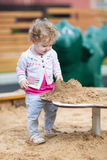Cute curly baby girl playing with sand on a playground Royalty Free Stock Photos