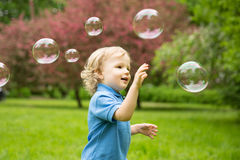 Cute curly baby with soap bubbles. children playing. Running A child playing outdoors in the flowering trees in the spring summer garden.  Springtime or Royalty Free Stock Photo