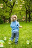 Cute curly baby with soap bubbles. children playing. Running A child playing outdoors in the flowering trees in the spring summer garden. Springtime or stock photography