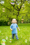 Cute curly baby with soap bubbles. children playing. Running A child playing outdoors in the flowering trees in the spring summer garden. Springtime or royalty free stock photos