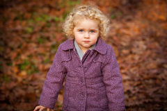 Cute curly baby staying at leafs Stock Images