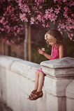 Cute curly blonde child girl in pink outfit sitting on the wall under blooming tree Stock Image