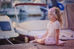 Cute curly blonde child girl in pink skirt sitting in docks Royalty Free Stock Photography