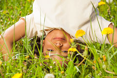 Cute curly boy stands upside down in field Stock Photos