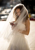 Cute curly bride with long veil looking at bouquet Royalty Free Stock Images