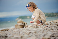 Cute curly child girl building stone tower on summer sea side Stock Photo