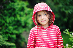 Cute curly child girl close up portrait in rainy summer garden Royalty Free Stock Images