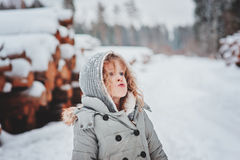 Cute curly child girl portrait on the walk in snowy winter forest Stock Image