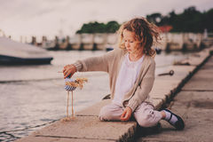 Cute curly child girl relaxing on seaside and playing with toy bird. Royalty Free Stock Photo