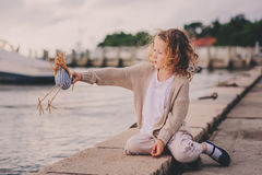Cute curly child girl relaxing on seaside and playing with toy bird. Royalty Free Stock Photos