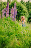 Cute curly child girl smells flower on summer field Royalty Free Stock Photo