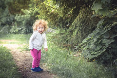 Cute curly child girl walking alone in forest on footpath among trees  during summer holidays symbolizing happy carefree childhood Royalty Free Stock Image
