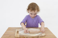 Cute curly child rolling out dough Royalty Free Stock Images