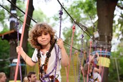Cute curly child in a rope park Royalty Free Stock Image