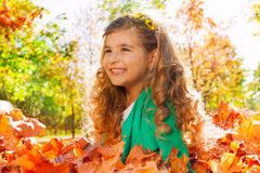 Cute curly girl close-up view in golden leaves Royalty Free Stock Photos