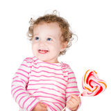Cute curly girl with a heart shaped candy Royalty Free Stock Photos
