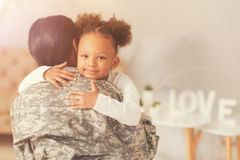 Cute curly girl hugging her mother in military uniform. Happy child. Pretty curly girl hugging her mother wearing a military uniform after her long period of Royalty Free Stock Photos