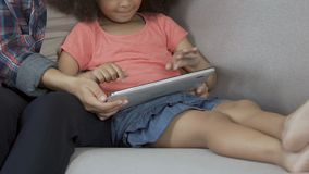 Cute curly girl playing game on tablet home, having fun with mother, parenting