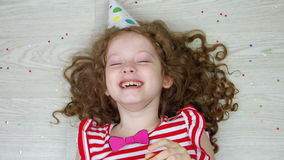 Cute curly girl playing and laughing in carnival party. High top view.