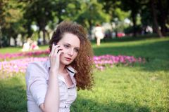 Cute curly girl talking on the phone Stock Photography