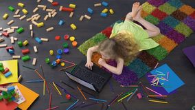 Cute curly girl using educational software on laptop, learning numbers at home. Stock footage stock footage