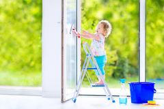 Cute curly girl washing a window in white room Royalty Free Stock Images