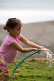 Cute curly girl watering flowers in the garden Stock Image