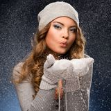 Cute curly girl wearing mittens during snowfall Royalty Free Stock Photos