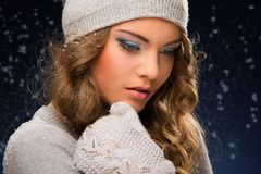 Cute curly girl wearing mittens during snowfall Stock Photo