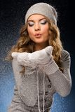 Cute curly girl wearing mittens during snowfall Royalty Free Stock Image