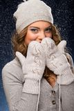 Cute curly girl wearing mittens during snowfall Stock Images